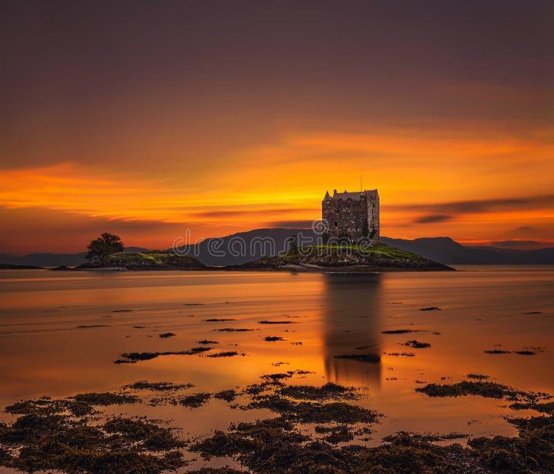 在城堡潜随猎物者的日落海湾的Appin在苏格兰,英国 图库摄影