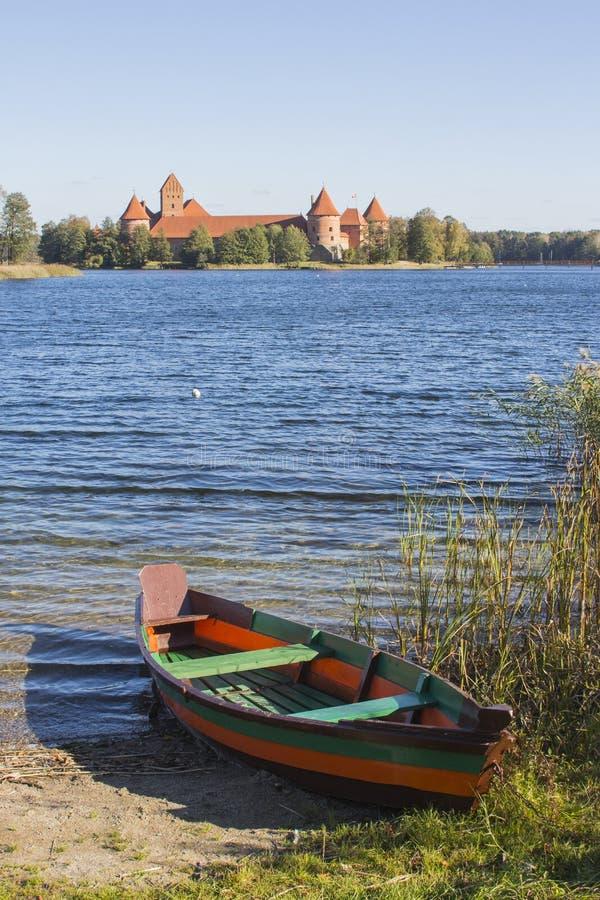 在城堡的背景的一条五颜六色的木小船在特拉凯 r 库存图片