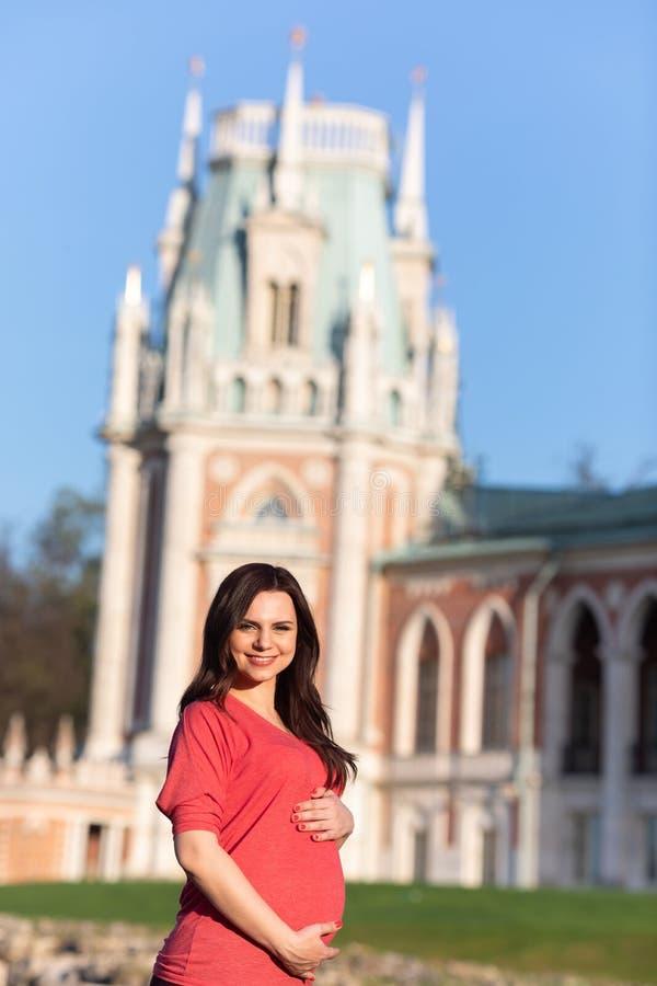 在城堡附近的怀孕的女孩 免版税库存图片