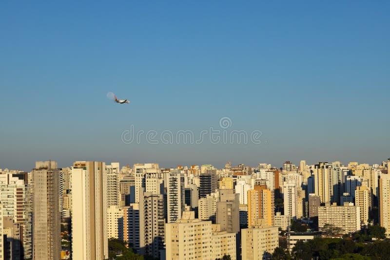 在城市、飞机和月亮的美好的风景在一好日子 免版税库存图片