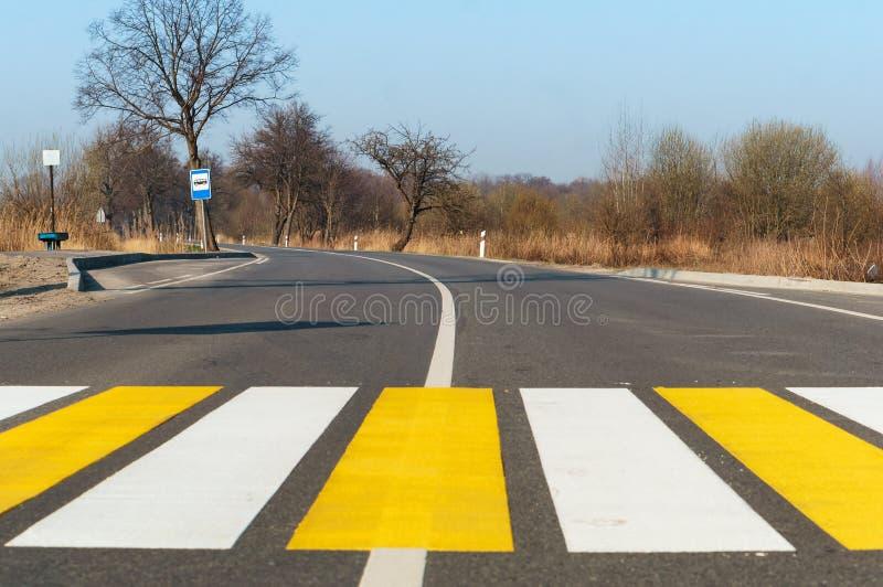 在城市之外的行人交叉路,在路的白色黄色标号 免版税库存图片