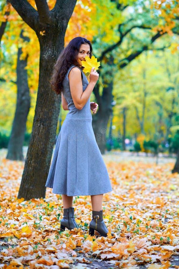 在城市公园里与秋叶一起摆姿势的女人 图库摄影