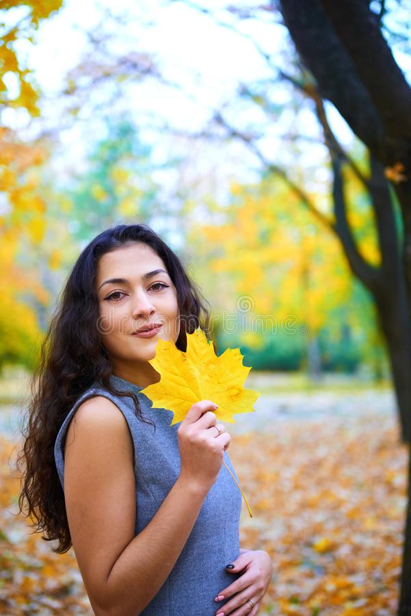 在城市公园里与秋叶一起摆姿势的女人 免版税库存照片