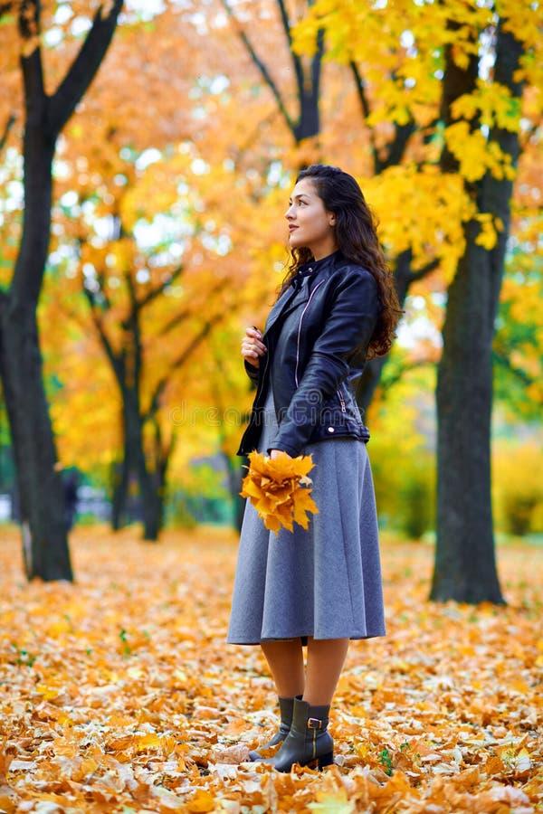 在城市公园里与秋叶一起摆姿势的女人 免版税库存图片