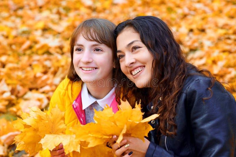 在城市公园里玩秋叶的女人,户外肖像 库存图片