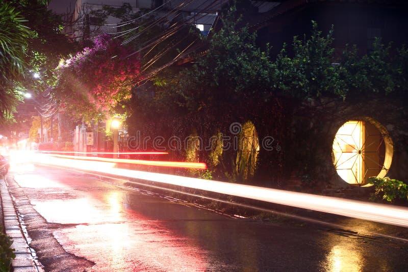 在城市和在多雨天气的运动的运输夜街道上的看法有灯笼的 r 免版税库存图片