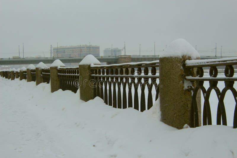 在城市堤防的积雪的篱芭 免版税图库摄影