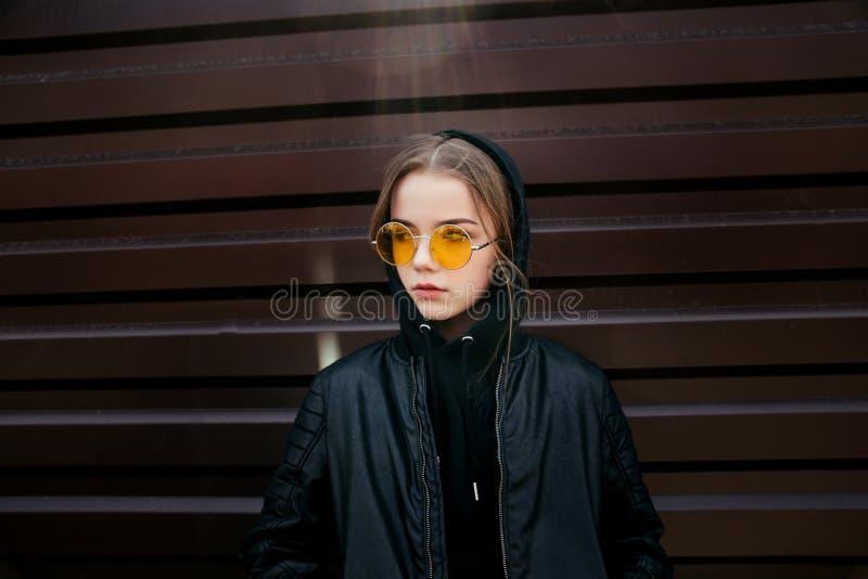 在城市塑造孩子概念-戴黑便衣和太阳镜的时髦的女孩孩子摆在夏天 库存照片