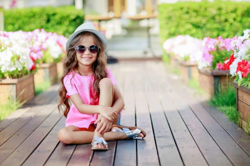 在城市塑造戴一副桃红色方格的衬衣、帽子和太阳镜的小女孩模型 库存照片
