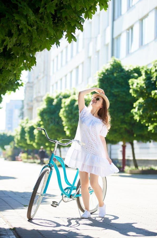 在城市拿着自行车和帽子的街道lookingup的女性身分 库存照片