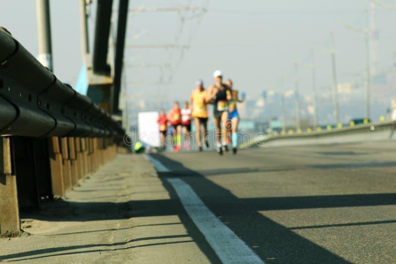 在城市桥梁的Blured athlets r 马拉松通过城市路  库存照片