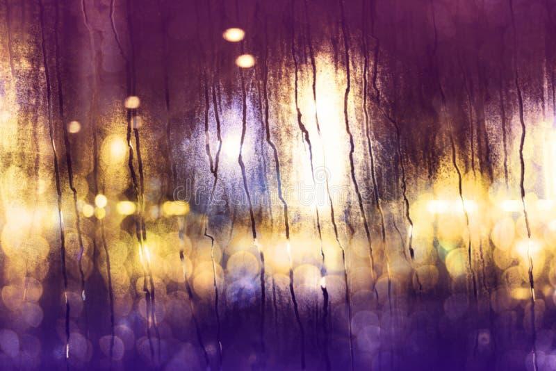 在城市概念的下雨天 在玻璃窗的雨珠 作为外部看法的被弄脏的都市光 库存图片