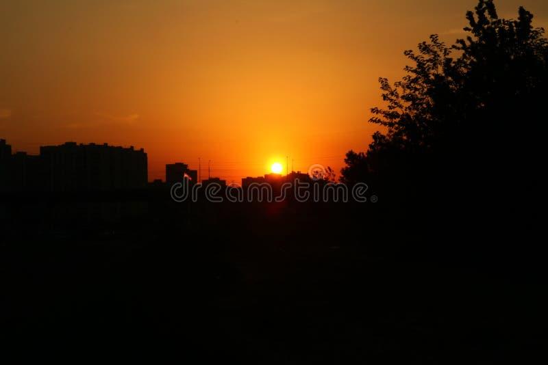 在城市橙色,圆的太阳和城市的剪影的日出 免版税库存图片