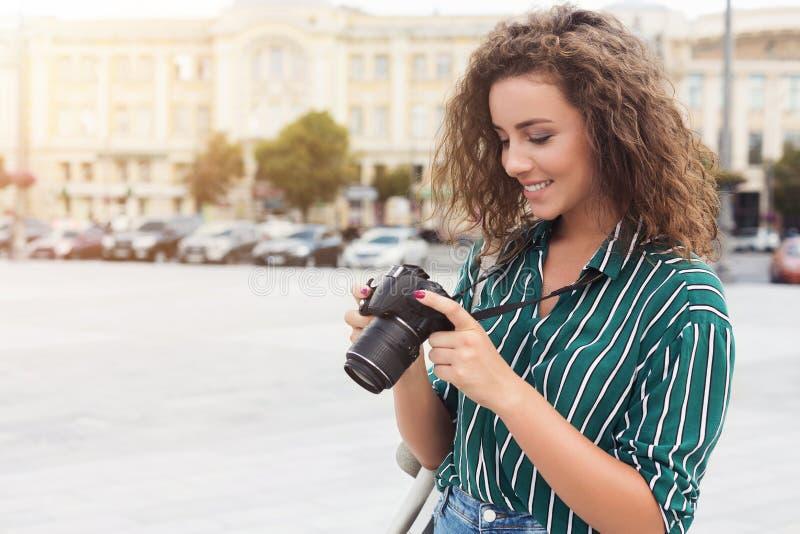 在城市步行期间的迷人的女性摄影师照相 库存照片