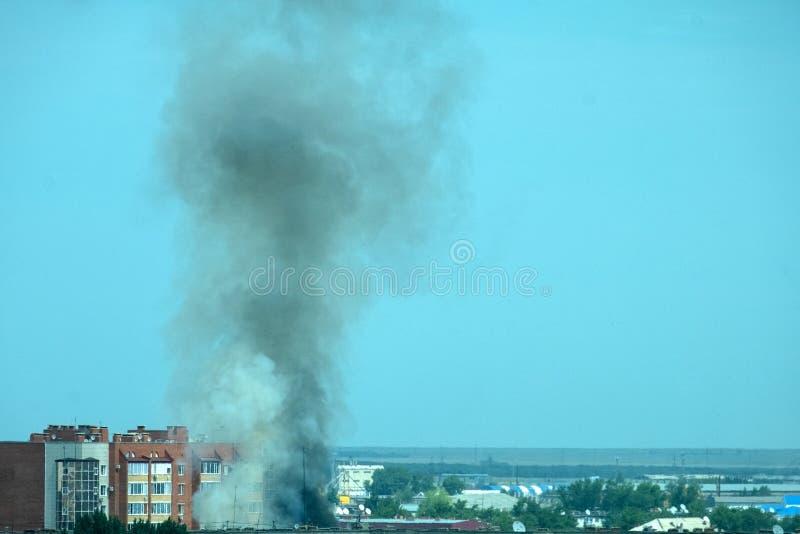 在城市火的鸟瞰图 在污染大气和环境的住宅块的屋顶的上浓烟 库存照片