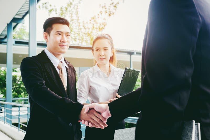 在城市的亚洲企业握手在办公室成功概念之外 库存图片