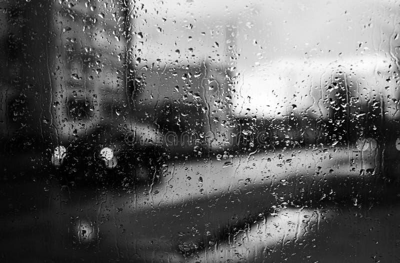 在城市的熙来攘往的背景的雨珠 库存图片