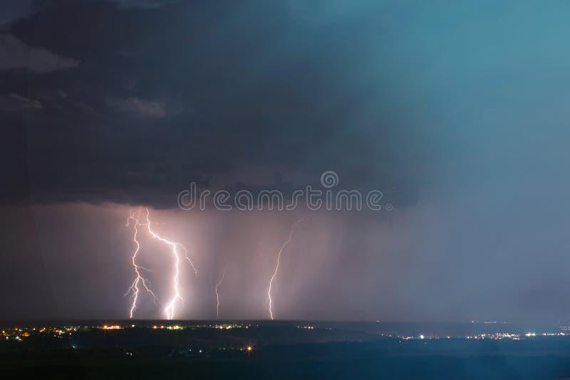 在城市的闪电风暴 在深蓝天空的雷击在夜城市 库存照片