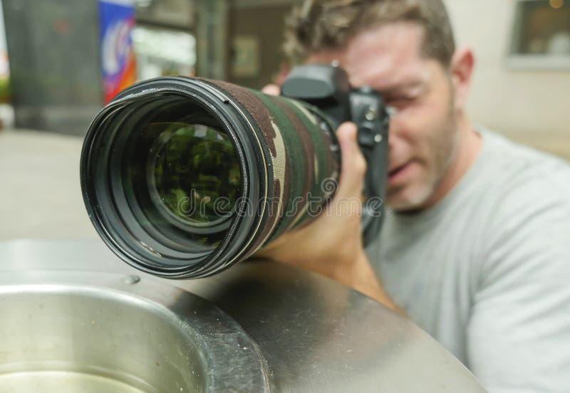 在城市纸篮子后行动的掩藏的年轻无固定职业的摄影师摄影师人生活方式滑稽的画象偷偷靠近为射击excl 免版税库存图片