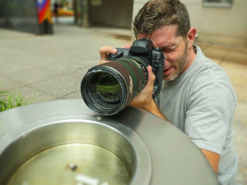 在城市纸篮子后行动的掩藏的年轻无固定职业的摄影师摄影师人生活方式滑稽的画象偷偷靠近为射击excl 库存图片