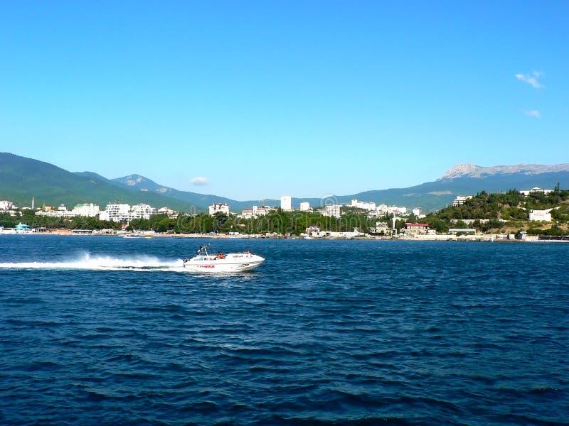 在城市背景的浮动白色汽艇沿海岸区的有大山的 免版税库存图片