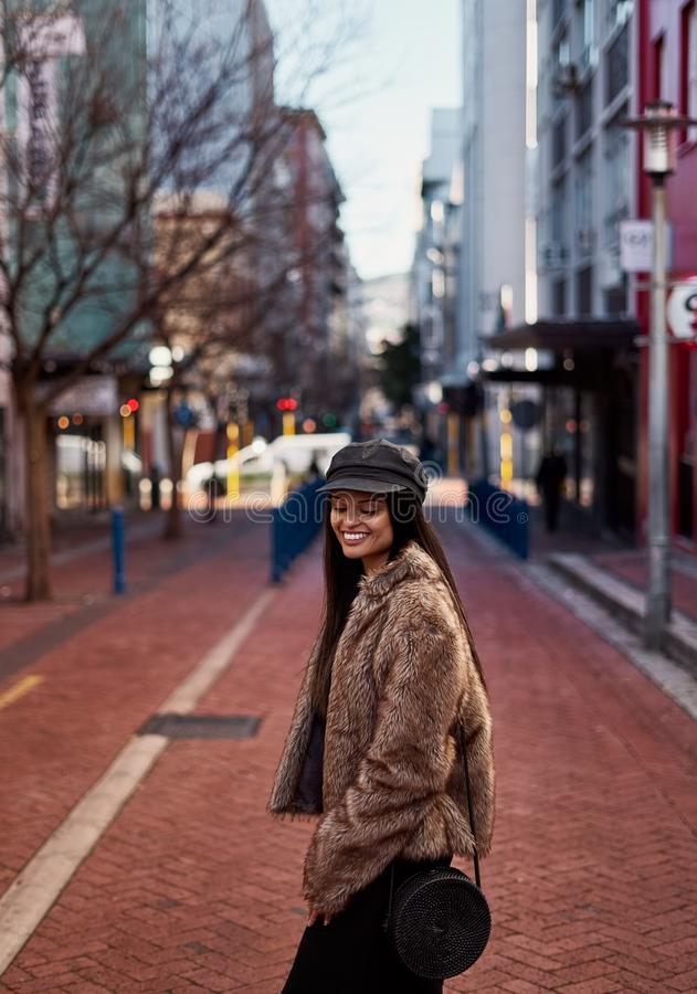 在城市街道上的俏丽的美丽的年轻深色的妇女 免版税库存图片