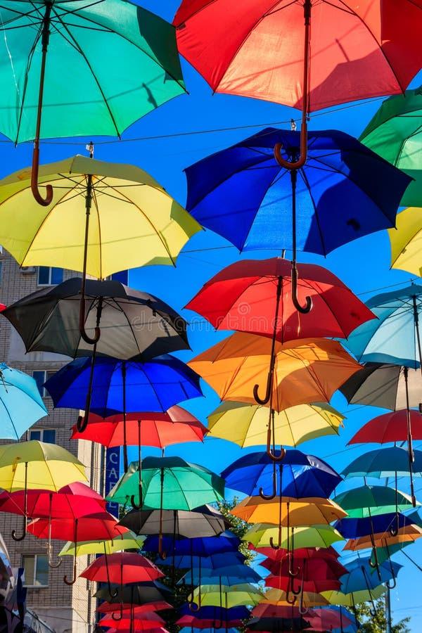 在城市街道上的多彩多姿的伞 城市街道用许多五颜六色的开放伞装饰 库存图片