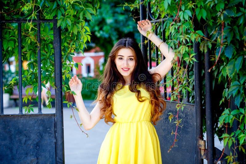 在城市街道上的女孩在黄色礼服的夏天 免版税库存照片