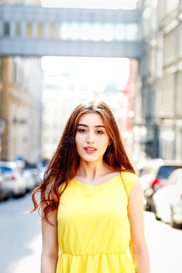 在城市街道上的女孩在黄色礼服的夏天 免版税图库摄影