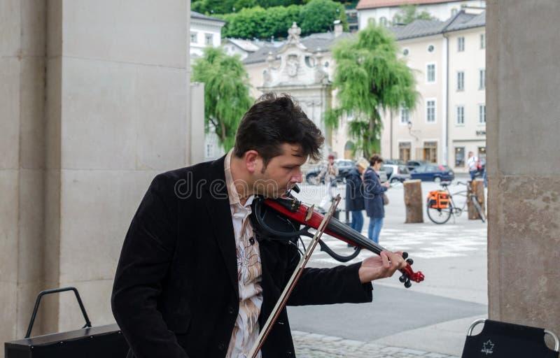 在城市街道上的小提琴球员戏剧古典音乐 萨尔茨堡 免版税图库摄影