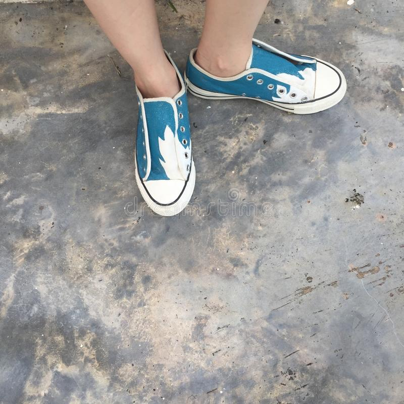 在城市街道上的少妇白色和绿色运动鞋 方式 库存照片