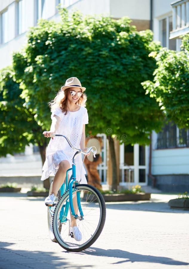 在城市街道上的年轻女性骑自行车者晴朗的夏日 免版税图库摄影
