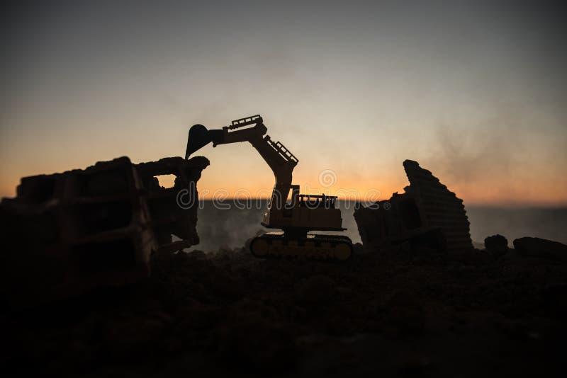 在城市街道上的建造场所 一种黄色挖掘机的挖掘机在建造场所夜间停放了 工业概念t 免版税库存照片