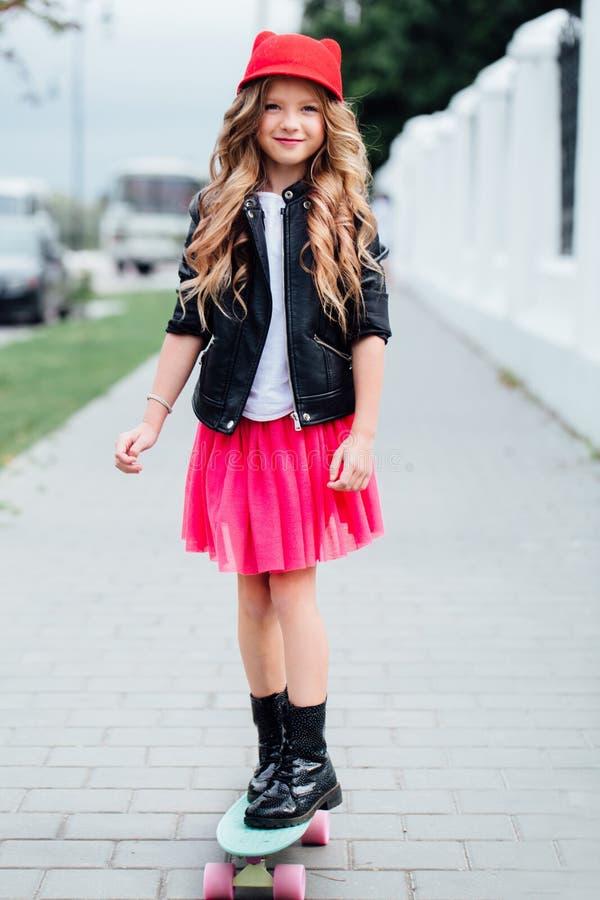 在城市街道上的时髦的时尚小女孩儿童骑马滑板 红色帽子,黑骑自行车的人夹克 免版税库存图片