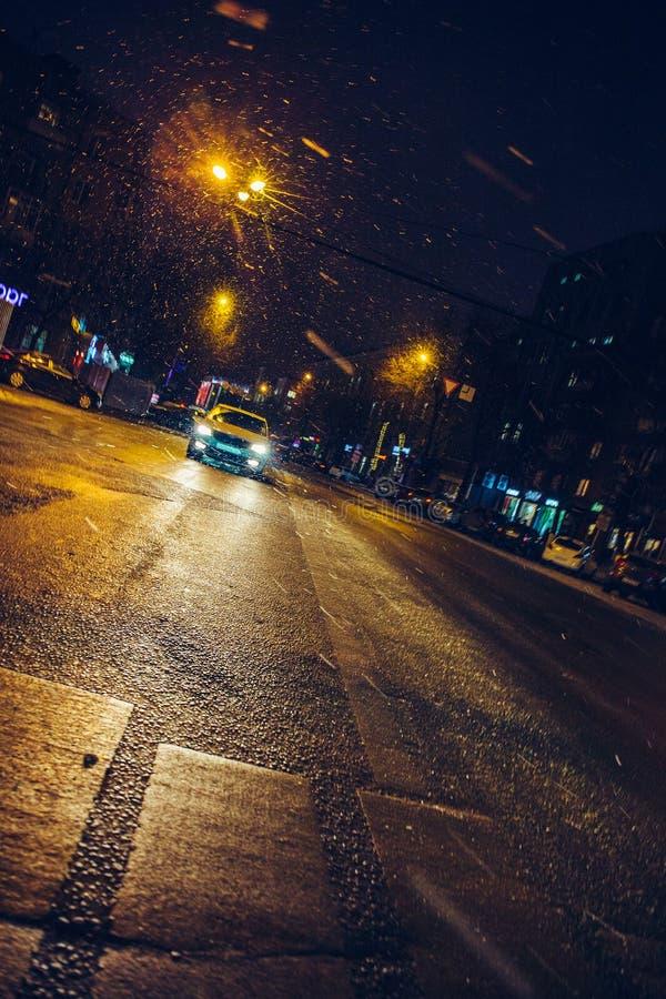 在城市街道上的汽车乘驾在夜、冬天都市路光和运输概念 免版税库存图片