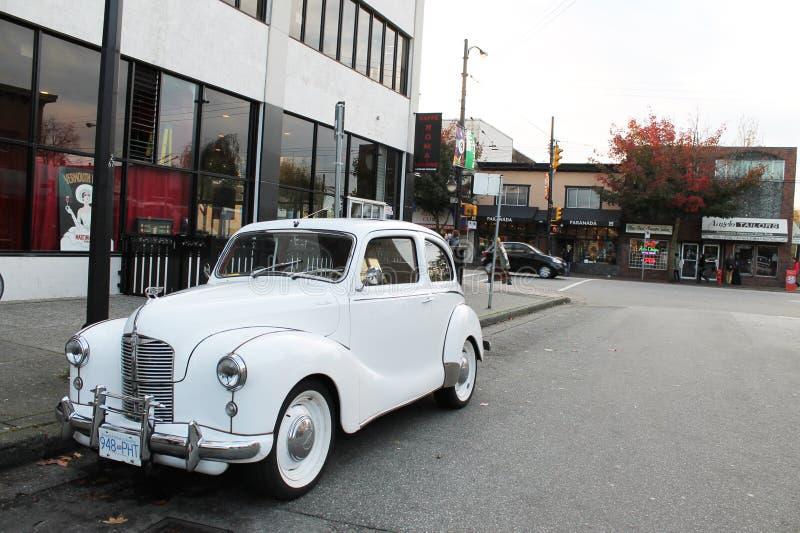在城市街道上的白色古色古香的奥斯汀汽车 库存图片