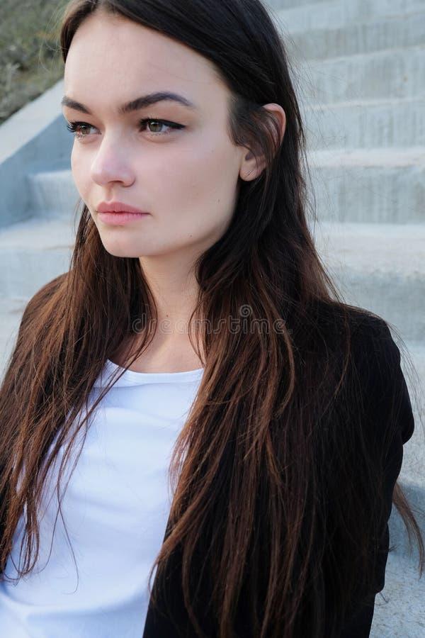 在城市街道上的美丽的女孩 穿戴在人的样式 免版税库存照片