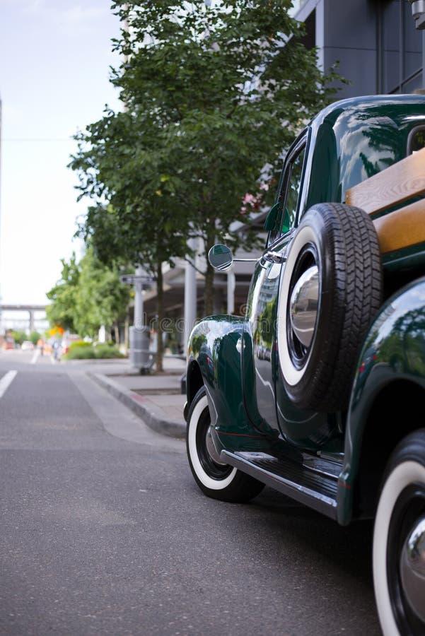 在城市街道上的绿色减速火箭的卡车 图库摄影