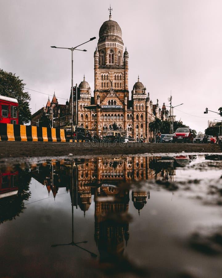 在城市街道中间这个更旧的大厦,复杂地被设计,伸手可及的距离到灰色天空里 正它的图象是reflecte 库存照片