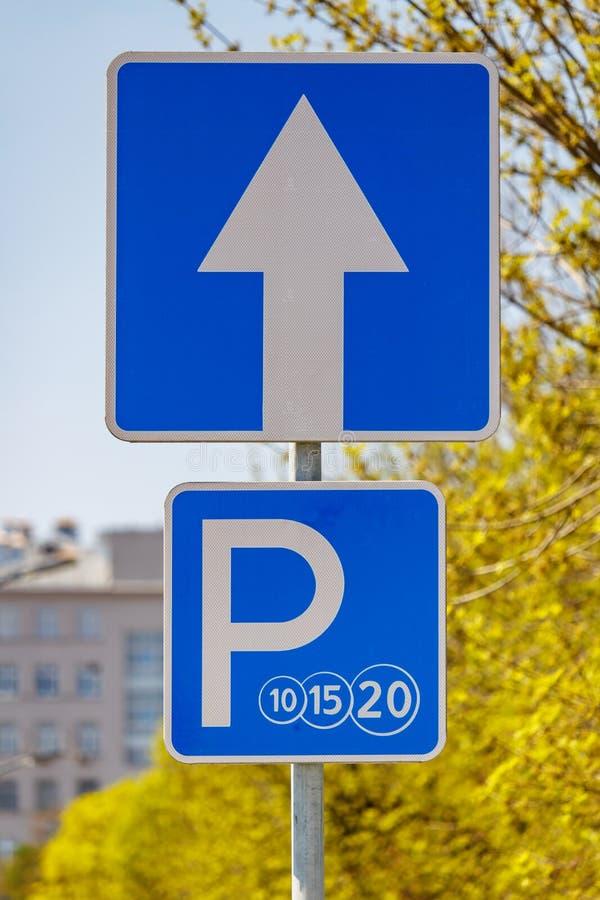 在城市街道反对绿色树和天空蔚蓝上的路标被支付的停放的特写镜头在好日子 库存照片