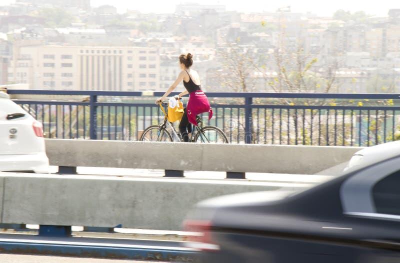 在城市街道桥梁车道的一辆年轻女人骑马自行车 免版税库存图片