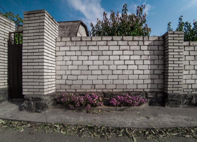 在城市街道的白色砖砖墙 免版税库存照片