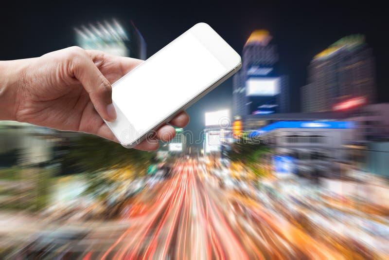 在城市递拿着智能手机用交通堵塞 图库摄影