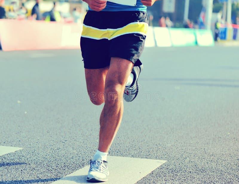 在城市道路的赛跑者脚在马拉松连续种族 免版税库存图片