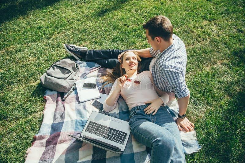 在基于草坪的爱的年轻夫妇在研究以后 免版税库存照片