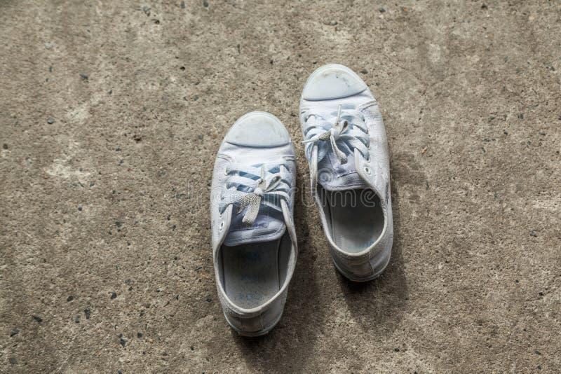 在基本上混凝土的老运动鞋 库存照片