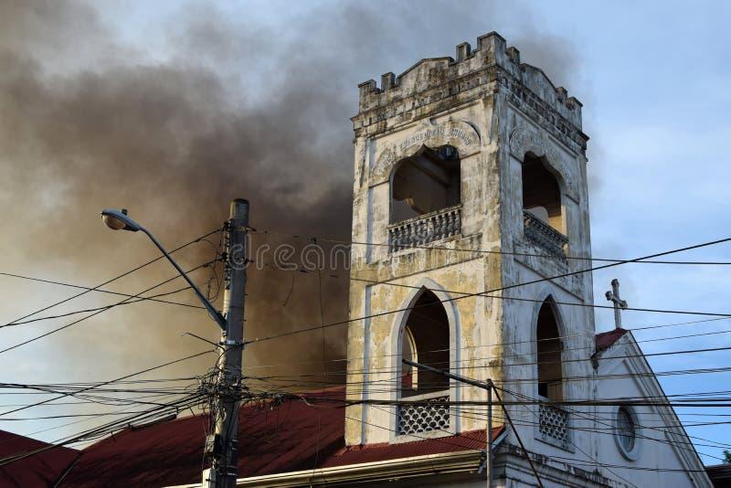 在基督教会塔后的厚实的黑烟在毁坏内部简陋小木屋的火安置 库存照片