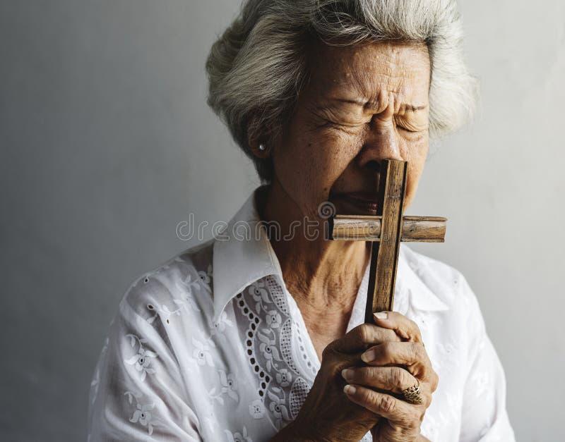 在基督教宗教的资深妇女祷告信念 免版税库存图片