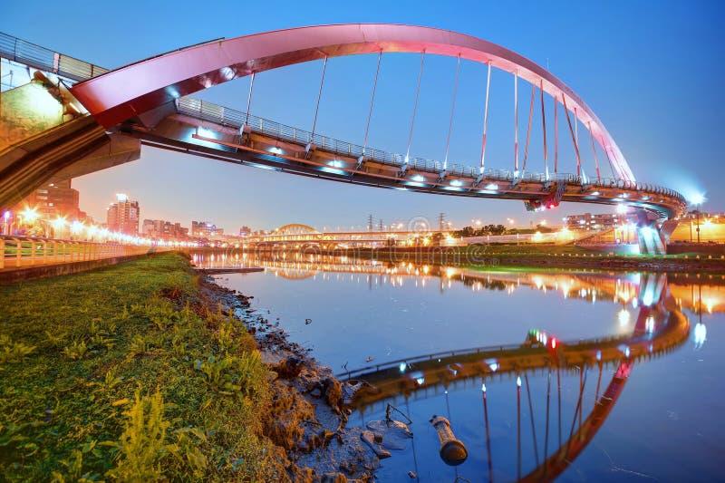 在基隆河的著名彩虹桥有在光滑的水的反射的在黄昏在台北,台湾亚洲 免版税库存图片