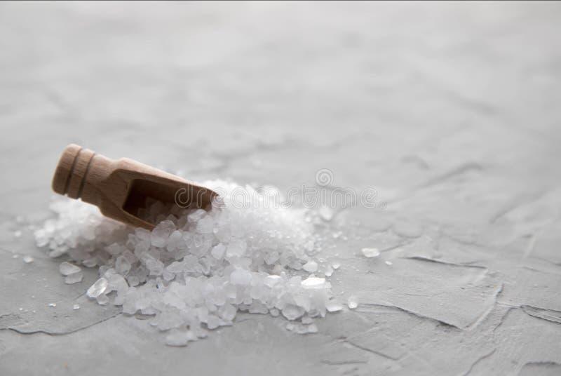 在堆困住的木瓢海盐白色水晶在具体背景 木铁锹在堆非常突出海 免版税库存照片